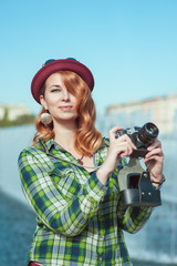 Hipster redhead girl in hat and glasses with retro camera