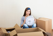 Smiling girl with clock sitting on floor among moving boxes