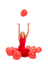 woman plays with red balloons