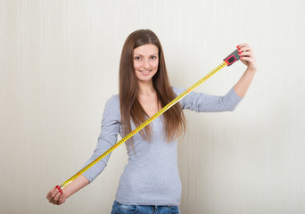 Portrait of a smiling girl extending a tape measure out