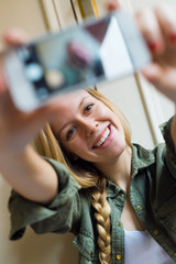Young beautiful woman taking a selfie with smartphone in her new