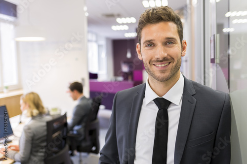 Leinwanddruck Bild Portrait of smiling Businessman posing  in modern office, lookin