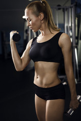 Athletic young lady doing workout with weights