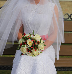 Bright festive wedding bouquet in hands of the bride in a dress