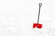 Red plastic shovel with black handle stuck in fluffy snow. - 76362586
