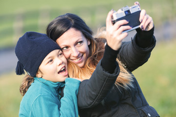 woman and child shooting a selfie with camera