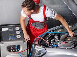 Car mechanic checks the air handling unit of a car