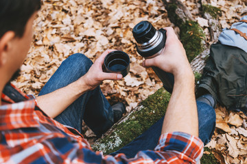 Hiker man holding a cup of tea and thermos in autumn forest