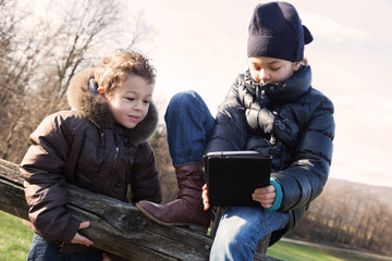 two children playing with the tablet in outdoor