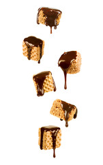 Chocolate syrup pouring over a sweet wafer cookies