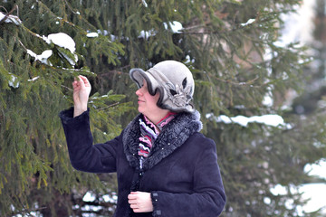 The woman in a hat and a sheepskin coat costs near a fir-tree in