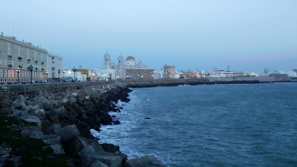 Ocean   embankment and Cathedral in  evening time. Cadiz, Spain