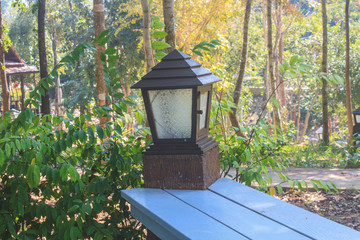 lantern on the log pole of wooden bench
