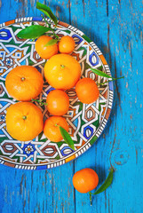 tangerines  with leaves in plate  on wooden background, in blue