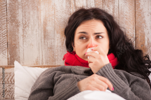 Young sick girl lying in bed - 76369198