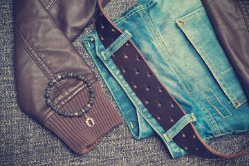 jeans with a belt, leather jacket, bracelet on the arm