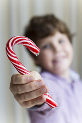 Child holding a candy cane