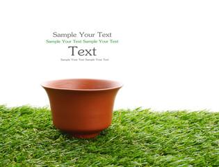 clay tea cup on green field