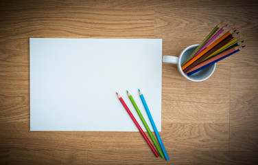 Color pencils in white coffee cup and white paper