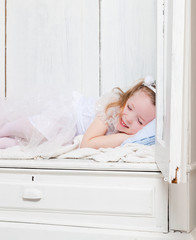Little girl sleeping in wardrobe