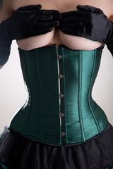 Beautiful topless woman in green corset