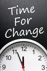 The phrase Time For Change on a blackboard above a clock