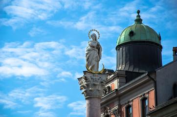 Lady statue on a pole with blue sky