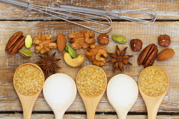 Sugar, nuts and whisk on rustic wooden surface