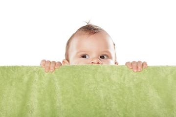 cute baby boy peek behind the green towel