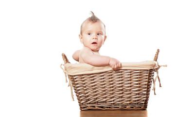 sweet little baby boy sitting in a wicker basket