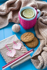 A cup of tea in sweater with lemon, old notebook