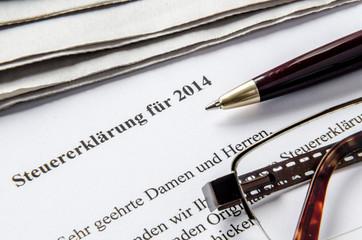 Steuererklärung 2014 mit Stift Brille und Zeitung