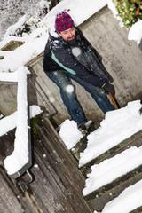 Mann schaufelt Schnee von einer Treppe
