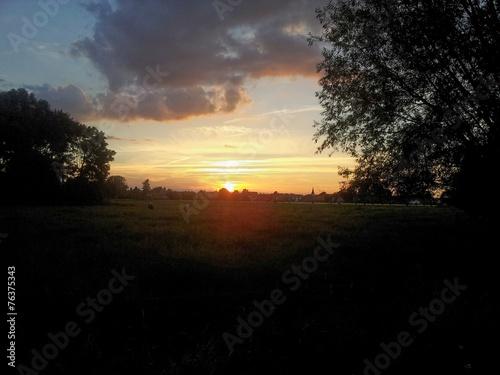 canvas print picture Sonnenuntergang über einer Wiese