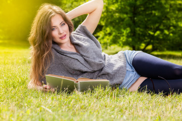 Woman reading book lying down on grass in park