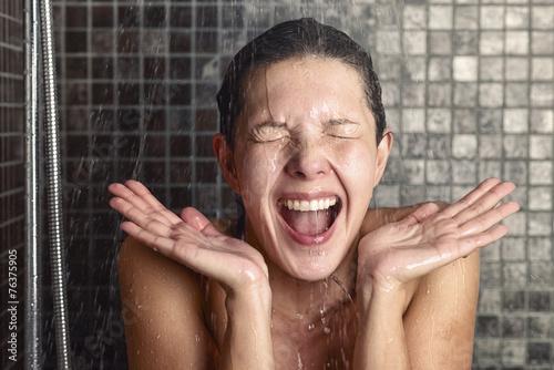 Junge Frau reagiert überrascht auf heißes oder kaltes Wasser - 76375905