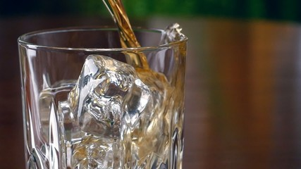 Pouring a scotch whiskey into glass with ice