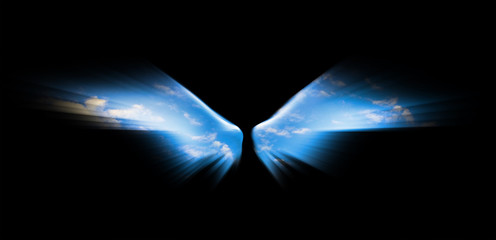 Angel wings isolated on black background and blue sky is visible