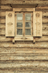 Windows with shutters, patterned on the wall of the old wooden h