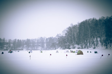 Many flags and tents on the snow-covered field near the forest