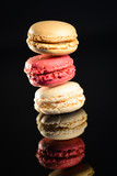 stack of colorful french macaroon on black background