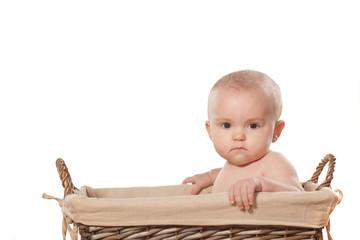 sweet little baby girl sitting in a wicker basket
