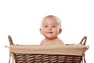 happy little baby girl sitting in a wicker basket