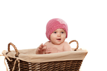 happy little baby girl sitting in a wicker basket