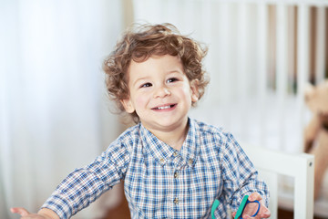 Portrait of happy smiling beautiful little boy in babyroom