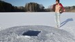 Young man swimming in the winter pond's ice hole at sunny day