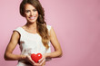 Attractive young woman in pink dress with heart on Valentine Day