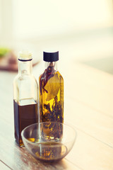 close up of two olive oil bottles and bowl of oil