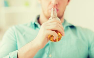 close up of man drinking beer at home