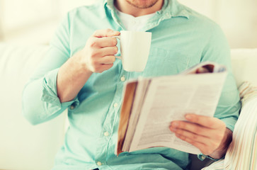 close up of man with magazine drinking from cup